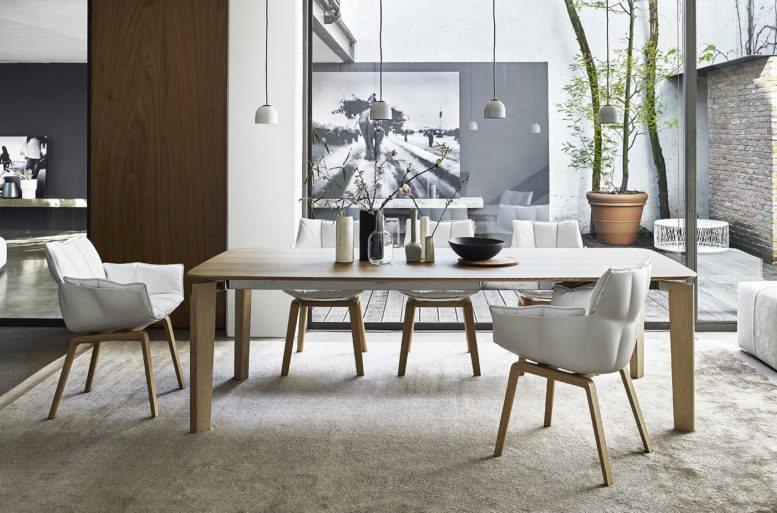 Giocata nei toni chiari del bianco e tinta legno la sala da pranzo. Le proporzioni, i giochi di volumi e le finiture la rendono estremamente personalizzabile.  Tavolo Oskar, tappeto Suavis.