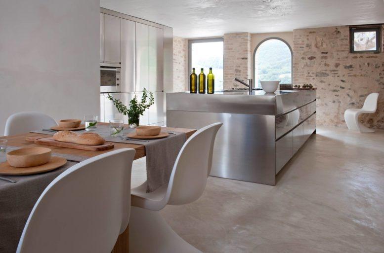 La cucina è interpretata come un ambiente aperto, libero e fruibile, pensato su misura per le esigenze dell'abitare moderno. Il piano di lavoro è funzionale a tutte le attività del contenere, preparare, cucinare e si adatta ogni giorno alle necessità dello stare insieme e del vivere la casa. Isola Convivium di Arclinea, tavolo Seven per B&B Italia di Jean Marie Massaud, sedia Papilio per B&B Italia di Naoto Fukasawa.
