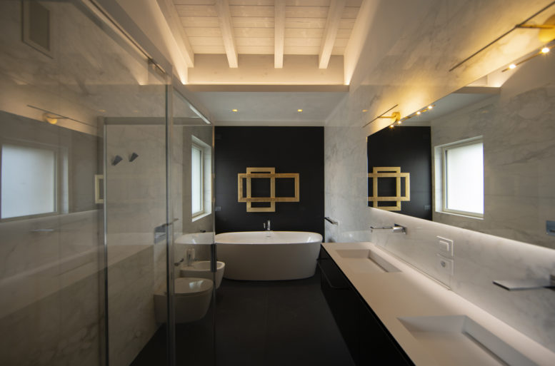 Gold, velvet, fine leather and wood in warm tones, colors that also enter the master bathroom where the protagonist is the radiator in gold leaf finish that stands out on the wall covered in black granite.