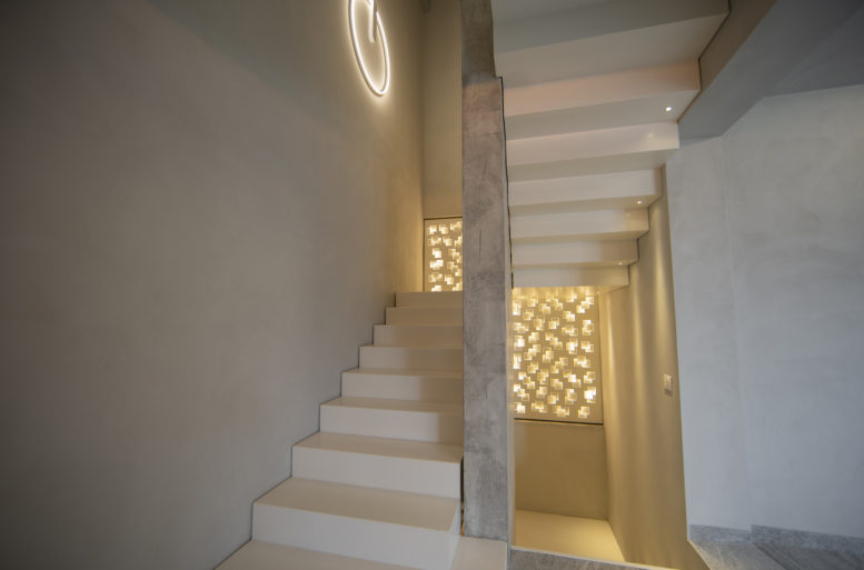 Behind the very fine leather sofas, the white-painted iron staircase seems to float in space, aided by the luminous metal wall. This creates a play of light and shadows. The staircase is double sided and also visible from the entrance and decorates the space.